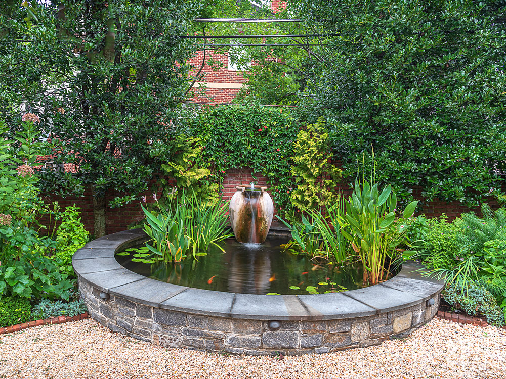 After shot of brick wall with fountain and koi pond installed